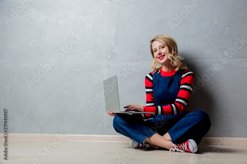 Portrait of a young style blonde girl in red striped sweater with laptop computer on grey background.