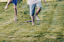 Children Playing With The Garden Sprinkler Jumping Over With Wet Clothes. Body Parts, Close Up Of Legs And Feet.
