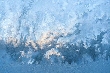 Fototapeta Frosty pattern, similar to the artist's palette, on window lit by winter sun.
