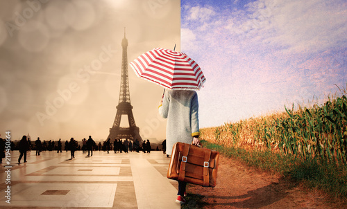 Obraz Young girl in coat with suitcase and umbrella walking along a rural road on one side and parisian square on other. - fototapety do salonu