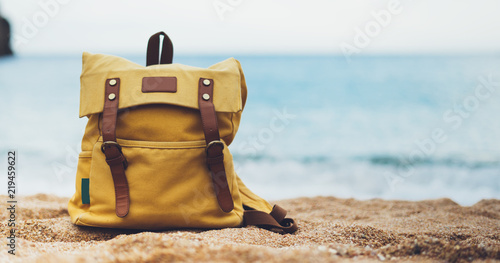 Hipster hiker tourist yellow backpack closeup on background blue sea ocean horizon on sand beach, blurred panoramic seascape blank, traveler relax holiday concept, sunlight view in trip vacation