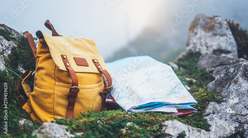 Hipster hiker tourist yellow backpack and map europe on background green grass nature in mountain, blurred panoramic landscape, traveler relax holiday concept, view planning wayroad in trip vacation