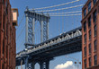 View of the Manhattan Bridge between two red brick buildings