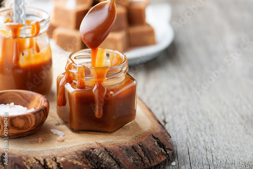 Fotografía  Homemade salted caramel sauce in jar on rustic wooden table.