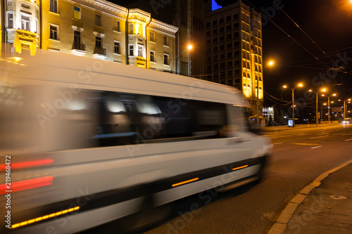 Vászonkép Motion blurred white minibus on the street in the evening.