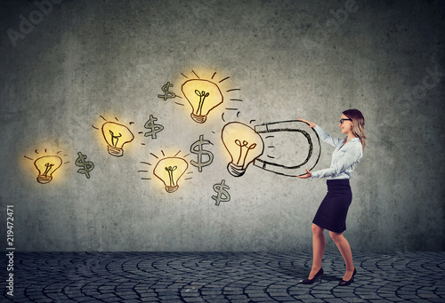 Photo Businesswoman attracts bright ideas light bulbs with a big magnet