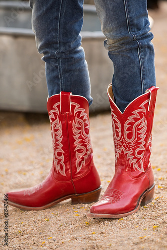 Female in red cowboy boots on gravel road Wallpaper Mural