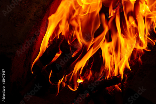 Poster Fire / Flame Fire from charred logs. Fire burns in the dark. Fire on a dark background. The flame from the campfire.