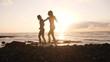 Slow motion, women dance on beach at sunset