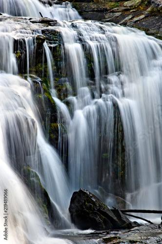Fotografie, Obraz  Mountain waterfall dropping over smooth moss rocks in blurred motion
