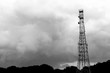 monochrome silhouetted telecommunications mast sited on farmland