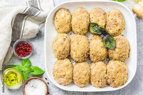 Photo Healthy oven baked chicken rissoles on baking dish, ready for cooking