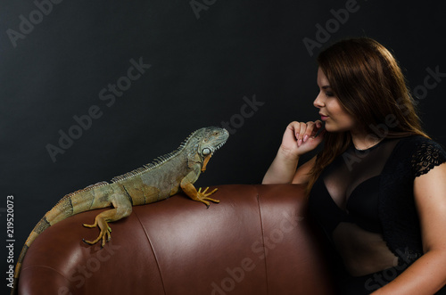 beautiful big tits girl and green iguana in the studio