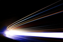 Interesting And Abstract Light Trails In Orange, Blue And White In A Dark Car Tunnel. Art Image That Can Be Used As Background Or Texture