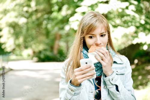 Fotografiet  Young woman eating fast food outdoor and talking on telephone gadget