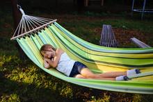 Tired Scool Girl Relaxing Outdoor. Child Sleeps In A Hammock In The Garden.