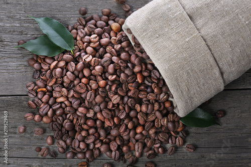 Coffee beans in burlap sack on wood background Tapéta, Fotótapéta