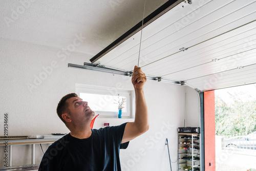 man opens pvc garage door manually Wallpaper Mural