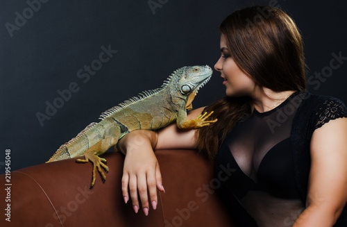 perfect sensual girl and big green iguana in the studio