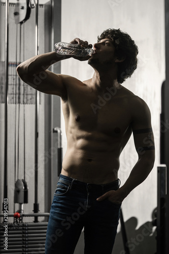 Poster Bestsellers Young adult male drinks bottle of water in gym