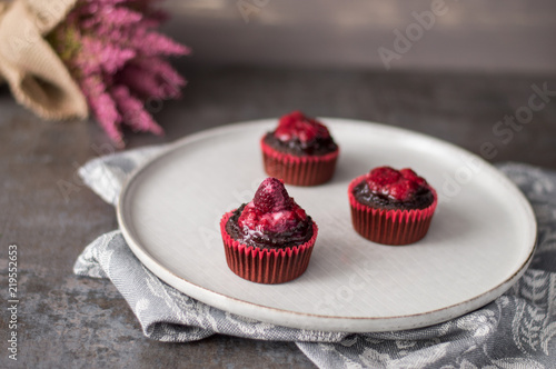 Fotografia  Cupcakes with raspberry chocolate topping