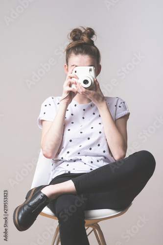 Cool Young Woman In Black And White Outfit Sitting On A Chair Photographing With Instant Camera Studio Lighting No Retouch Matte Filter Kaufen Sie Dieses Foto Und Finden Sie Ahnliche Bilder