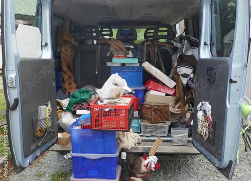 offener, unordentlicher Kofferraum eines Lieferwagens, beladen mit alten Werkzeugen, Schrott und Müll