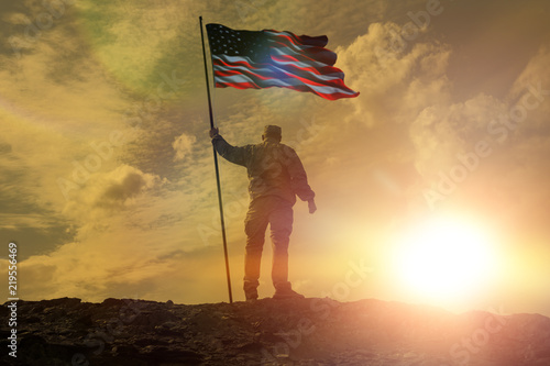Silhouette of man holding US flag American on the mountain Canvas Print