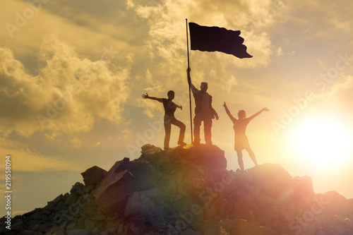 Silhouettes of happy three people on top of a mountain with the flag of victory Wallpaper Mural