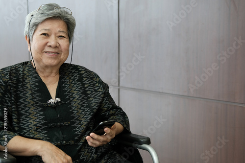 Photographie  elder woman on wheelchair holding mobile phone