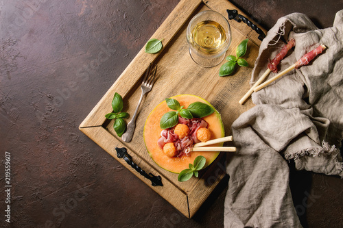 Melon and ham salad served in half of Cantaloupe melon with fresh basil and grissini bread on wooden serving tray over dark brown texture background with glass of white wine. Flat lay, space