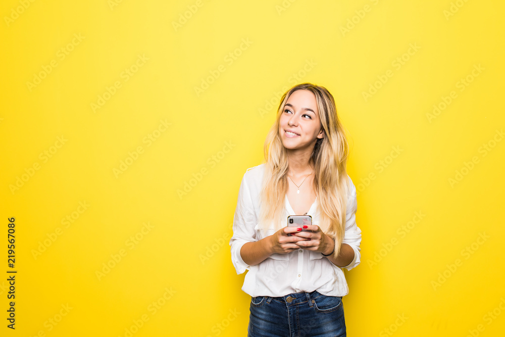 Fototapety, obrazy: Portrait of a young woman using mobile phone isolated over yellow background