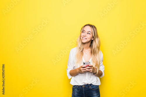 Portrait of a young woman using mobile phone isolated over yellow background