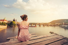 Young Woman Sitting On Wood Pier Looking Prague Castle, Prague River Vltava And Many Famous Prague Sights And Historic Architecture, Back View.