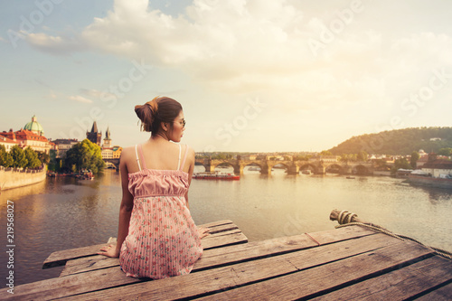 Photo Young woman sitting on wood pier looking Prague Castle, Prague river Vltava and many famous Prague sights and historic architecture, back view