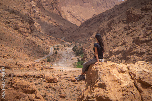 Foto  A woman relaxing over a rock, connected with the surroundings of the spectacular scenery in Morocco