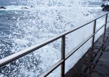 Dramatic White High Foaming Waves Crashing Over Steel Railings On A Jetty A The Edge Of A Summer Blue Sea