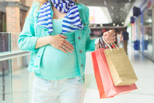 Fototapety, obrazy: Beautiful pregnant woman with paper packages in the mall