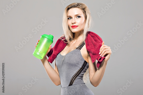 Fotografia  Charming model posing in the studio with a shaker in her hands and a towel aroun