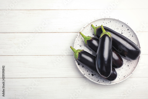 Plate with raw ripe eggplants on wooden background, top view