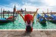 Glückliche Touristin mit rotem Hut genießt die Aussicht auf die Gondeln vom Markusplatz in Venedig, Italien