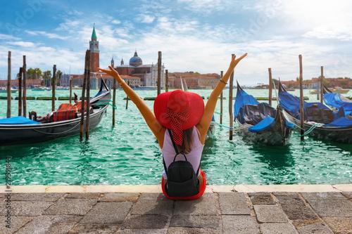 obraz dibond Glückliche Touristin mit rotem Hut genießt die Aussicht auf die Gondeln vom Markusplatz in Venedig, Italien