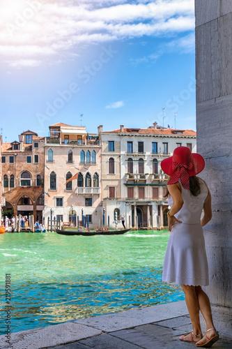 fototapeta na ścianę Attraktive, webliche Touristin im weißen Kleid schaut auf den Kanal Grande in Venedig an einem sonnigen Tag, Italien
