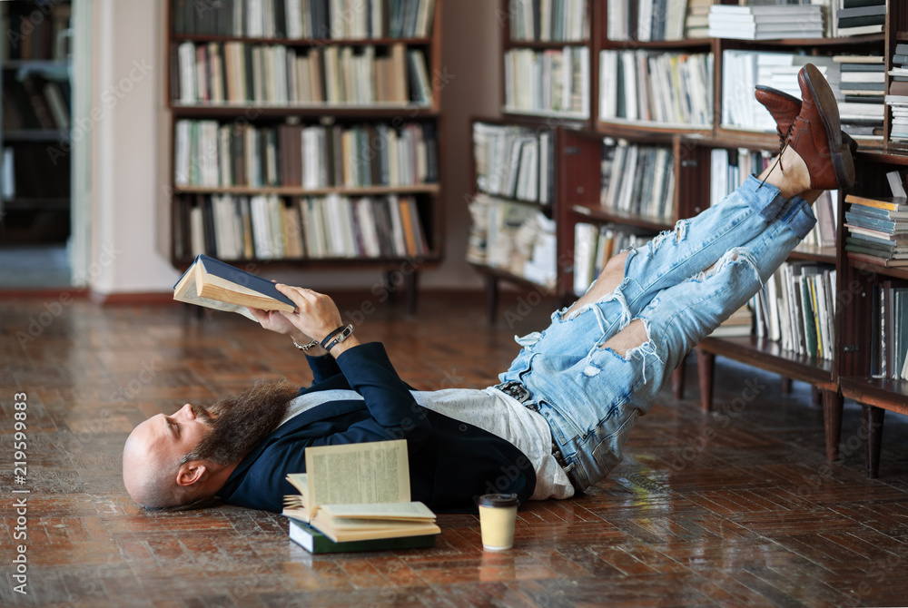 Fototapeta Bearded hipster man relax and reading book lies on the floor