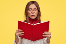 Youth, Intelligence, Knowledge, Studying And Emotions Concept. Scared Lovely Schoolgirl Holds Red Book, Afraids Of Tomorrows Exam At College, Has Fearful Expression, Isolated Over Yellow Background.
