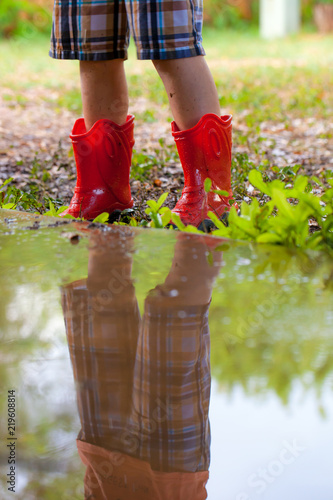 Fotografia, Obraz  Legs of child wearing pair of red rubber boots with reflection in water puddle