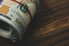 US Dollars In Roll On Money Background