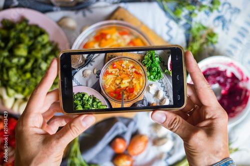 Woman hands make smartphone food photography of corn, potato
