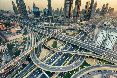 Aerial view of a big highway intersection in Dubai, UAE, at sunset. Transportation and communications concept.