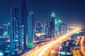 Scenic nighttime skyline of downtown Dubai, United Arab Emirates. Aerial view on highways and skyscrapers in the distance.